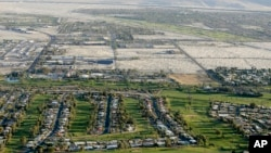 FILE - This aerial file photo shows lush green golf courses bordering the edge of the desert in Palm Springs, California, April 3, 2015.