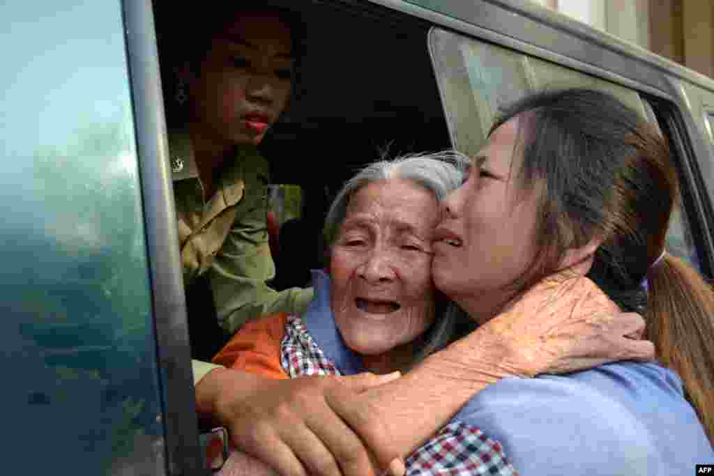 Nhà hoạt động vì quyền đất đai người Campuchia Nget Khun (giữa) ôm con gái (phải) qua cửa sổ xe tù tại Tòa phúc thẩm ở Phnom Penh. Tòa án Campuchia y án đối với 10 phụ nữ hoạt động vì quyền đất đai và một nhà sư hoàn tục và giảm mức án một năm cho hầu hết những người họ.