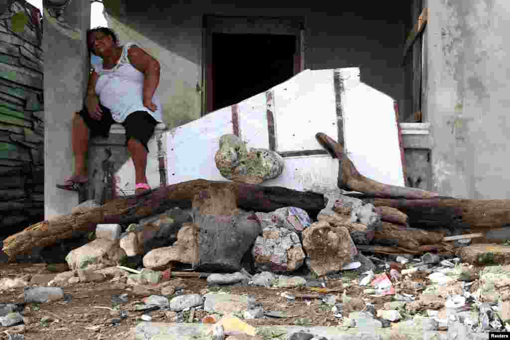A woman takes a break from cleaning the debris in front of a house, in the aftermath of Hurricane Irma in Puerto Plata, Dominican Republic.