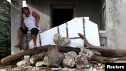 Một nạn nhân ở vùng Caribe bên đống đổ nát vì bão Irma ngày 8/9/17