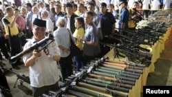 Philippine President Benigno Aquino (far L) talks to a religious leader while Al-haj Murad Ebrahim (2nd L), chairman of the Moro Islamic Liberation Front (MILF), inspects a B40 rocket launcher during the Ceremonial Turnover of Weapons and Decommissioning