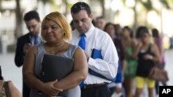 Fila de personas buscando trabajo en una feria de empleos en Miami, Florida.