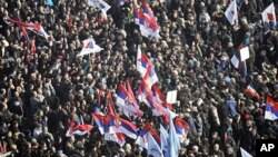 People waving Serbian flags crowd a square in front of the General Assembly building during an anti-government rally in Belgrade, February 5, 2011
