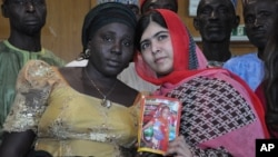 Pakistani activist Malala Yousafzai, who survived being shot by the Taliban because she advocated education for girls, holds a picture of kidnapped schoolgirl Sarah Samuel with her mother Rebecca Samuel, while visiting Abuja, Nigeria, July 13, 2014.