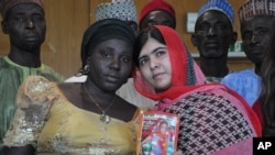 Pakistani activist Malala Yousafzai who survived being shot by the Taliban because she advocated education for girls, holds a picture of kidnapped schoolgirl Sarah Samuel with her mother Rebecca Samuel, during a visit to Abuja, Nigeria, July 13, 2014.