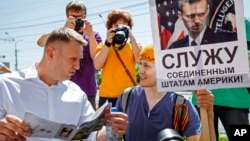 "Russian opposition activist and blogger Alexei Navalny, left, speaks to activists of a National Liberation movement holding a poster with a portrait of him and words reading ""Serve United States of America"" during his visit in Novosibirsk, Russia, Sunday,"