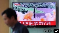 ຊາຍຄົນນຶ່ງຍ່າງກາຍຈໍໂທລະທັດທີ່ສະແດງໃຫ້ເຫັນລາຍການກ່ຽວກັບ ການທົດລອງລູກສອນໄຟຂີປະນາວຸດຂ້າມທະວີບ ຫລື ICBM ທີ່ສະຖານີລົດໄຟນະຄອນໂຊລ ຂອງເກົາຫລີໃຕ້ ໃນວັນທີ 5 ກໍລະກົດ 2017.