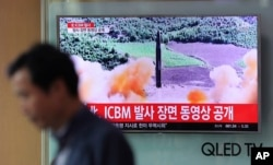 FILE - A man walks past a TV screen showing a local news program about North Korea's firing of an ICBM, at Seoul Train Station in Seoul, South Korea, July 5, 2017. The launch has prompted the U.S. to call for stronger sanctions against Pyongyang.
