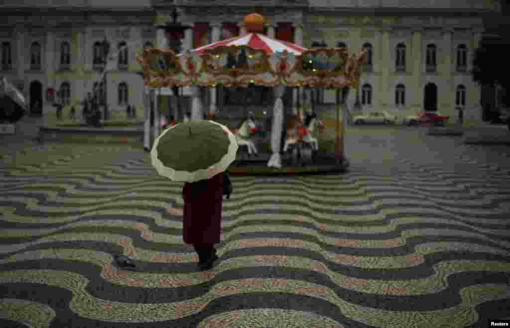 A woman walks near a merry-go-round at Rossio square in Lisbon, Portugal, January 16, 2013.