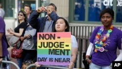 FILE- LGBT activists hold up a sign at the 44th annual San Francisco Gay Pride parade Sunday, June 29, 2014, in San Francisco, California.