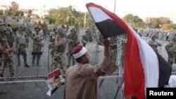 2013年7月7日,在埃及首都开罗,下台的穆尔西总统的支持群众连续3天进行抗议示威,有人高举埃及国旗表示支持穆尔西。