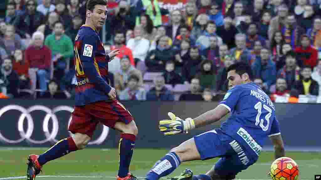 """Un but de """"Léo"""", Lionel Messi, à gauche, face au gardien Andres Fernandez de Grenade au cours d'un match de football de la Liga espagnole entre Barcelone et Grenade, au stade Camp Nou à Barcelone, Espagne, 9 janvier 2016."""