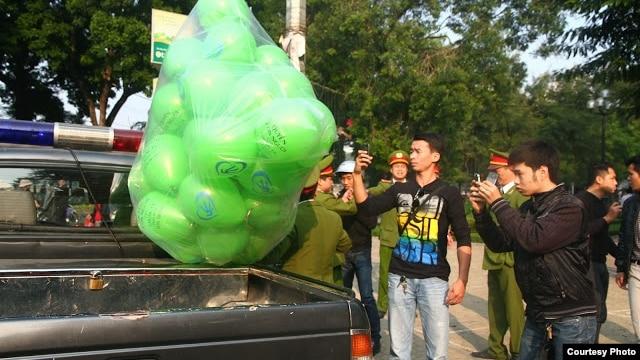 Bóng bay Nhân quyền bị Công an tịch thu đưa lên xe lôi về đồn (Ảnh: Danlambao)