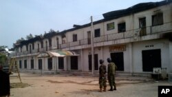 In this photo taken with a mobile phone, soldiers stand outside a burnt out shopping mall in Maiduguri, Nigeria, Monday, Oct. 8, 2012.