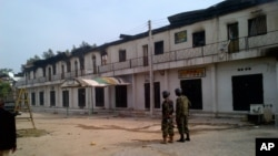 Tentara Nigeria berjaga di luar sebuah pertokoan yang terbakar di Maiduguri, Nigeria (8/10).