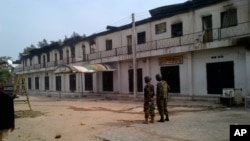In this photo taken with a mobile phone, soldiers stand outside a burnt out shopping mall in Maiduguri, Nigeria, October 8, 2012.