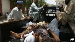 Pakistani villagers help victims from a blast to a district hospital in Landi Kotal Pakistan Afghanistan border, Saturday, June 16, 2012.