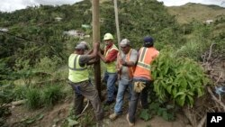Public Works Sub-Director Ramon Mendez, wearing hard hat, directs locals who are municipal workers, Eliezer Nazario, holding rope, Tomas Martinez, right, and Angel Diaz, left, as they install a power pole in an effort to return electricity to Felipe Rodri