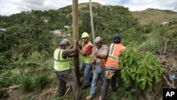 Public Works Sub-Director Ramon Mendez, wearing hard hat, directs locals who are municipal workers, Eliezer Nazario, holding rope, Tomas Martinez, right, and Angel Diaz, left, as they install a power pole in an effort to return electricity to Felipe Rodriguez's home, four months after Hurricane Maria in Coamo, Puerto Rico, Jan. 31, 2018.