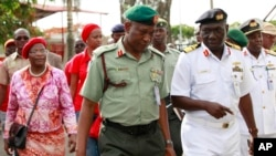 Brig. Gen. Chris Olukolade, Nigeria's top military spokesman, center, walks with representatives of kidnapped schoolgirls of Chibok secondary school, for a meeting at the defense headquarters in Abuja, Nigeria, May 6, 2014.
