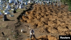 A worker prepares graves for inmates who died during a prison riot, at the cemetery of Taruma in Manaus, Brazil, Jan. 4, 2017.