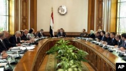 In this image released by the Egyptian Presidency, President Mohammed Morsi, center, meets with his Cabinet including new ministers at the presidential palace in Cairo, January 6, 2013.
