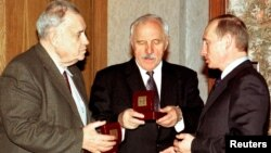 FILE - Russian President Vladimir Putin (R) gives birthday presents to Russian famous actor Mikhail Ulyanov (center) and famous movie director and producer Eldar Ryazanov (left) in his residence in Novo-Ogaryovo outside Moscow, November 20, 2002.
