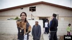Keluarga Israel berdiri dekat rumah mereka yang terkena roket tembakan kelompok militan Palestina dari Jalur Gaza, Rabu (23/3).