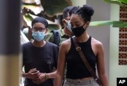 Desainer grafis Amerika Kristen Antoinette Grey (kiri) berjalan bersama rekannya Saundra Michelle Alexander (kanan) untuk tes COVID-19 di sebuah rumah sakit di Denpasar, Bali, Rabu, 20 Januari 2021.