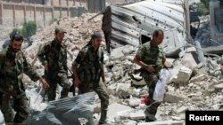 FILE - Forces loyal to Syria's President Bashar al-Assad walk with their weapons past rubble after they advanced on the southern side of the Castello Road in Aleppo, Syria, in this handout picture by SANA, July 28, 2016.