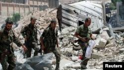 Pasukan pemerintah Suriah berjalan di antara reruntuhan bangunan di bagian selatan kota Aleppo (foto; dok).