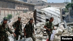 FILE - Forces loyal to Syria's President Bashar al-Assad walk with their weapons past rubble after they advanced on the southern side of the Castello road in Aleppo, Syria, in this handout picture provided by SANA on July 28, 2016.