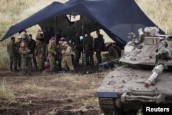 Izraelski vojnici stoje pored tenka u blizini izraelske granice sa Sirijom, na okupiranoj Golanskoj visoravni, 9. maja 2018.