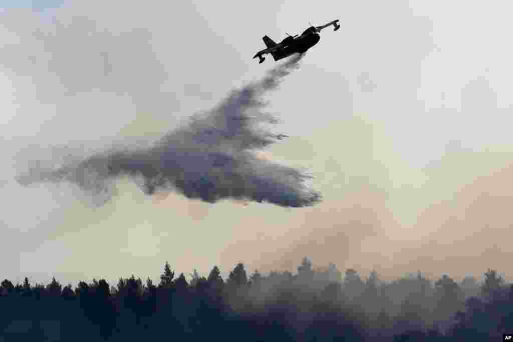 پاشیدن آب توسط یک هواپیما برای خاموش کردن آتش در نزدیکی شهر هالکیدا در یونان.