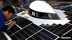 在上一届世界太阳能汽车挑战赛中,一名日本车手在擦拭赛车上的太阳能电池组件。(资料照)