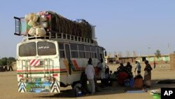 Southern Sudanese from Abyei, who have resided in the north for 21 years, wait next to a bus which will transport them back to the Abyei oil region, in Khartoum (File Photo)