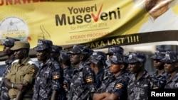 Policemen stand in front of an election banner of Uganda's President Yoweri Museveni in Kampala, Uganda, Feb. 15, 2016.