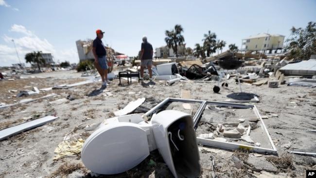 Los vecinos Bob Coleman, a la izquierda, y Ron Adkisson, registran los sitios de sus antiguas casas después del huracán Michael en Florida, el 17 de octubre de 2018.