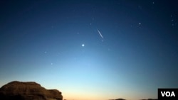 Sebuah meteor melintas di langit saat hujan meteor Perseid di Valley of Whales, di Fayoum, Egypt, 12 Agustus 2017. (H. Elrasam/VOA)