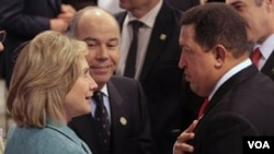 La secretaria de Estado, Hillary Clinton, dialoga con el presidente de Venezuela, Hugo Chávez, durante la toma de mando de Dilma Rousseff en Brasil.