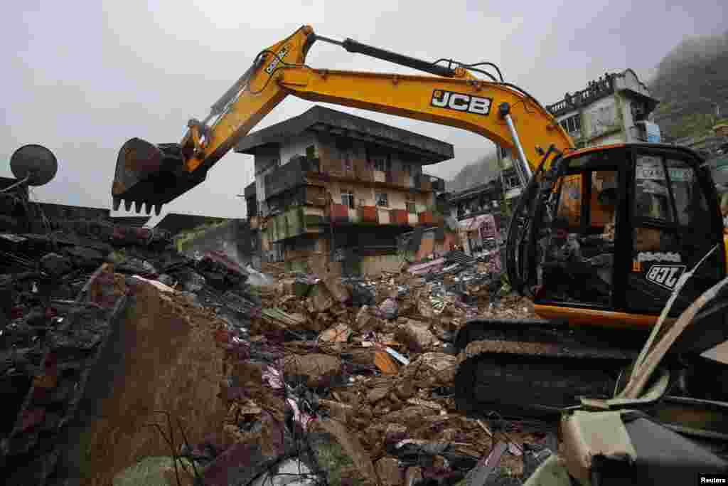 Rescue workers use an excavator to scour through the debris of a collapsed residential building on the outskirts of Mumbai, India, June 21, 2013.