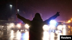FILE - A protester walks in the street with his hands up after the grand jury verdict in the Michael Brown shooting in Ferguson, Missouri, Nov. 26, 2014.