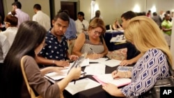 FILE - people fill out job applications at a job fair, in Miami Lakes, Fla.