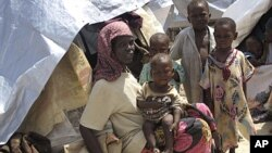 Somalis displaced by famine sit in their makeshift shelters in Mogadishu, Somalia, Friday, July 22, 2011