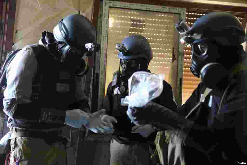 A U.N. chemical weapons expert, wearing a gas mask, holds a plastic bag containing samples from one of the sites of an alleged chemical weapons attack in the Ain Tarma neighborhood of Damascus. A team of U.N. experts left their Damascus hotel for a third day of on-site investigations into apparent chemical weapons attacks on the outskirts of the capital.
