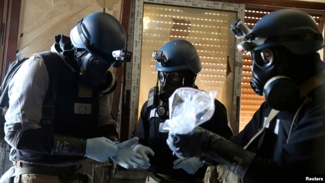 A U.N. chemical weapons expert, wearing a gas mask, holds a plastic bag containing samples from one of the sites of an alleged chemical weapons attack in Ain Tarma neighborhood of Damascus, Syria, Aug. 29, 2013.