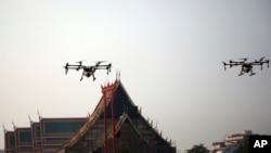 Beberapa drone terlihat menyemprotkan air, melintasi atap Kuil Suthat di Bangkok, Thailand, 31 Januari 2019.