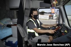 In this Monday, April 27, 2020, photo, truck driver Juan Giraldo poses for a photo inside his cab in Wilmington, California.