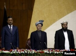 Afghanistan's President Ashraf Ghani, center, stands at attention for the national anthem during his visit at the joint National assembly gathering in Kabul, Afghanistan, April 25, 2016.