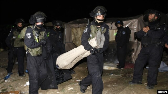 Israeli border police remove a Palestinian from an outpost of tents in an area known as E1, near Jerusalem, January 13, 2013.